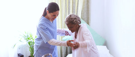 a nurse helping an elderly stand up