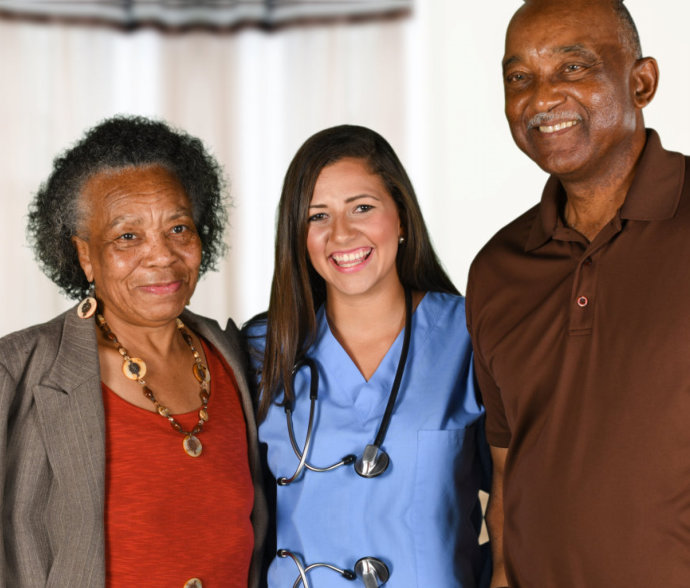 a nurse smiling with two seniors
