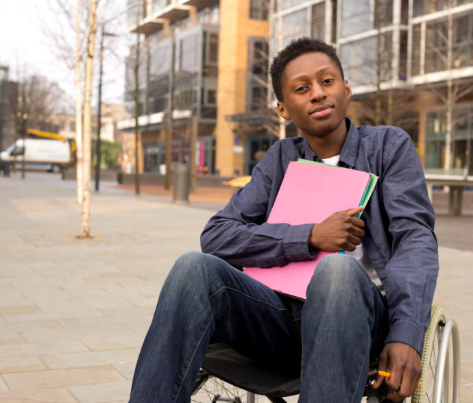 a disabled man on a wheelchair with a pink folder