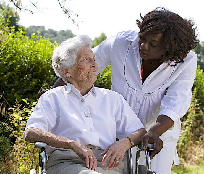 a senior on a wheelchair smiling at a nurse