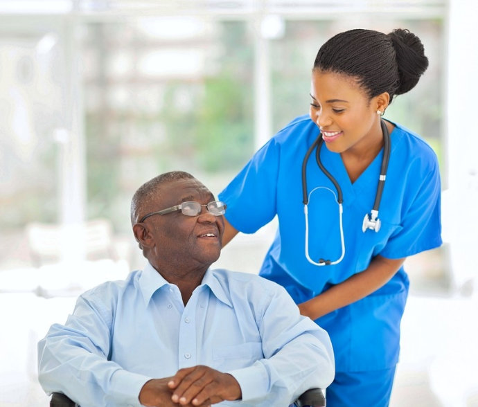 a nurse smiling at a senior with glasses